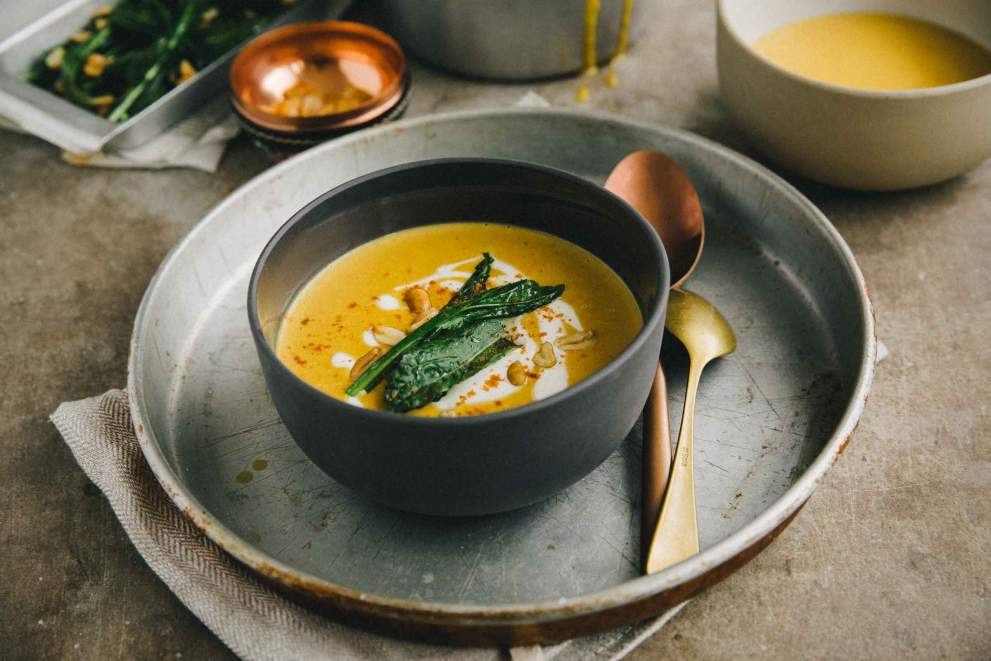 Pumpkin soup with roasted peanuts and kale served in a bowl