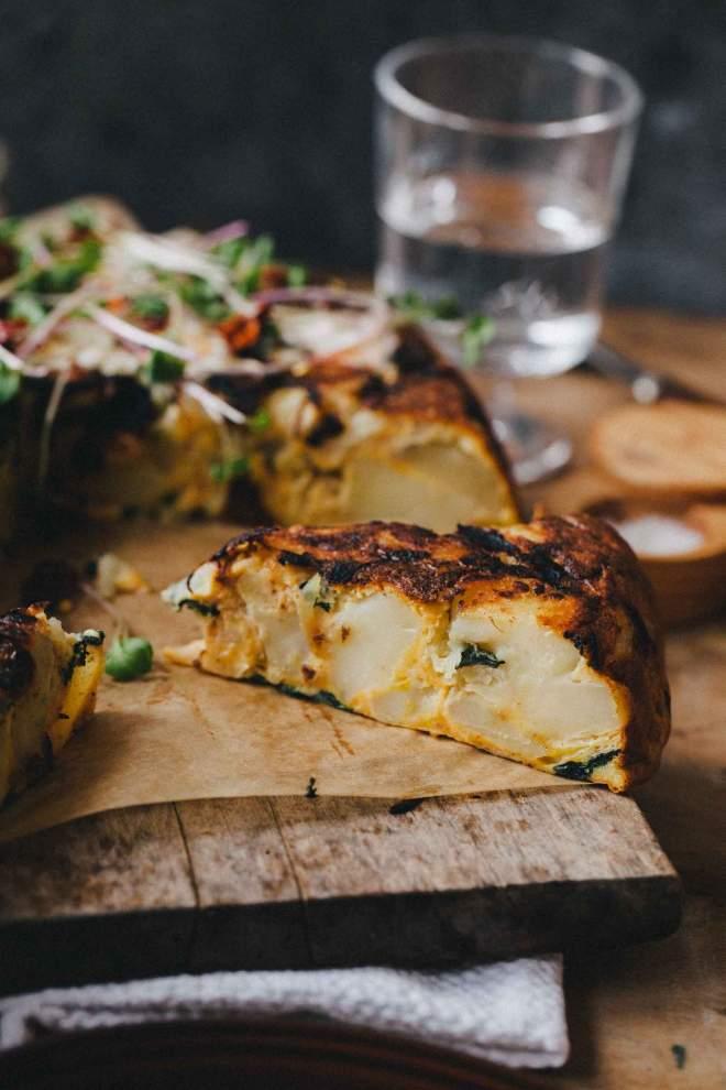 Krompirjeva tortilja narezana na kose in postrežena z zelišči
