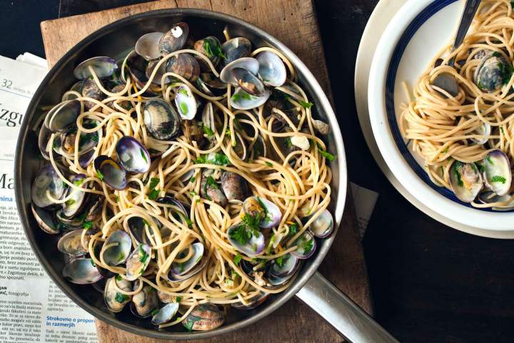 Spaghetti alle vongole served in a pan with parsley
