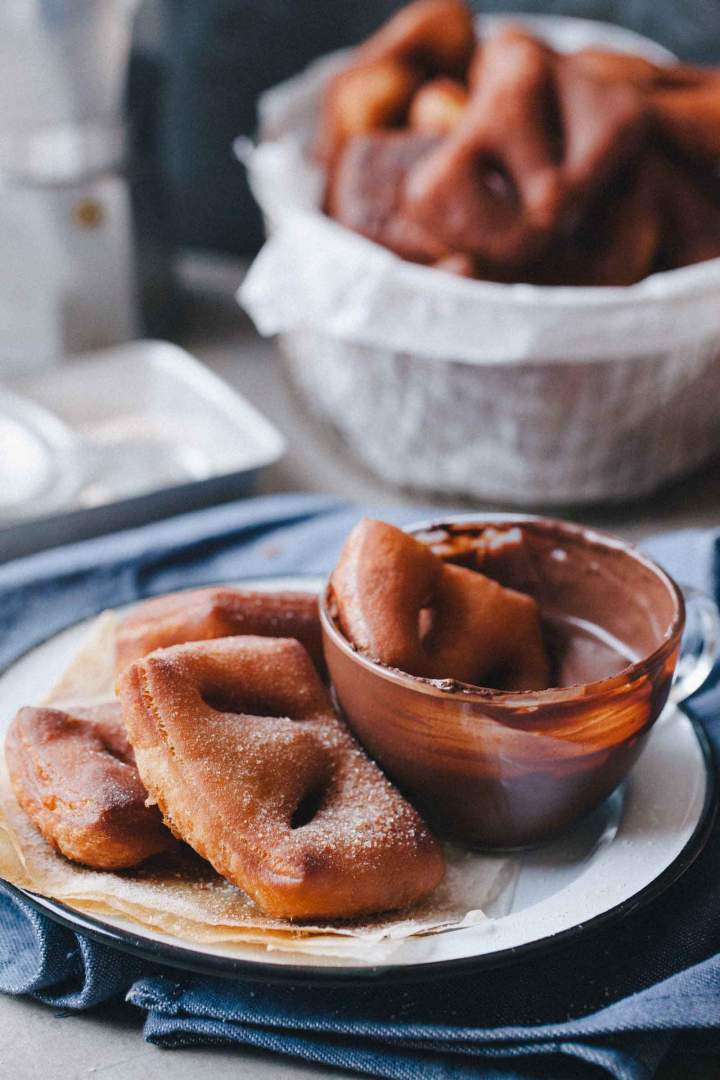 Beignets with cinnamon sugar on a plate with chocolate and coffee